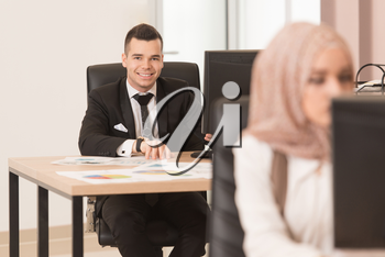 Happy Young Business Man And Muslim Woman Work In Modern Office On Computer