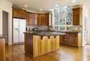 Modern Kitchen with Red Oak wooden floors, center gas stove island with stone counter tops and Daylight coming from large Vertical Windows