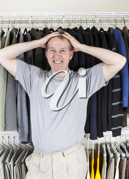Vertical portrait of mature Caucasian man in walk-in closet showing frustration with hands behind head while pulling his hair