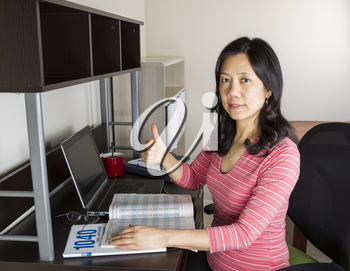 Mature Asian woman giving thumbs up with income tax tables booklet, computer, coffee cup and glasses on desk