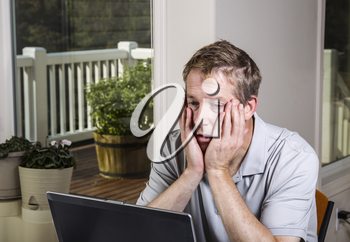Tired man looking at data results on computer at home