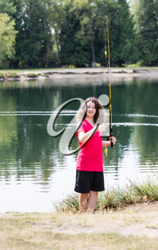 Vertical photo of young girl, looking forward, holding small fish that she caught with lake and trees in background