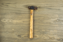 Horizontal photo of an old ball peen hammer on aged wood