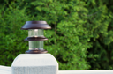 Horizontal photo of solar lamp, light just turning on, on patio post with green trees in background