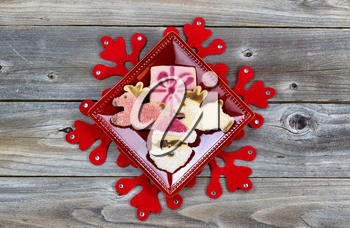 Top view of Christmas cookies in plate and large red snowflake with rustic wood underneath