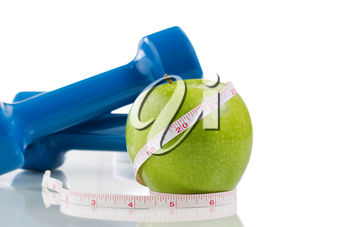 Pristine green apple, two dumbbells, measuring tape isolated on white with reflection. Plenty of copy space.