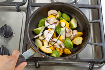 Close up of hand holding frying pan, focus on food, while cooking vegetables in pan on top of stove.