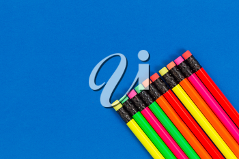 Office or back to school supplies consisting of colorful pencils in lower right corner on blue background.