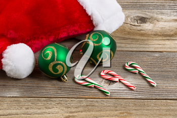 Close up of Santa Claus hat, green ornaments and candy canes on rustic wood