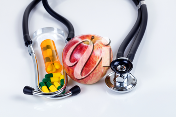 Red apple, medicine capsules and stethoscope on white table with reflection. Good health care concept.