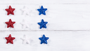 Stars in USA national colors on rustic white wooden boards. Fourth of July holiday concept for United States of America.
