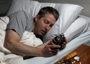 Mature man holding and staring at alarm clock while trying to fall asleep. Insomnia concept.