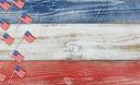 Flay lay view of USA mini flags on rustic wooden boards painted in red, white and blues colors.
