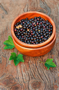 Sweet, black currant and green leaves in wooden bowl. Closeup. Selective focus.
