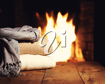Warm woolen things near fireplace on wooden table. Winter and Christmas holiday concept. Photo with retro filter effect.