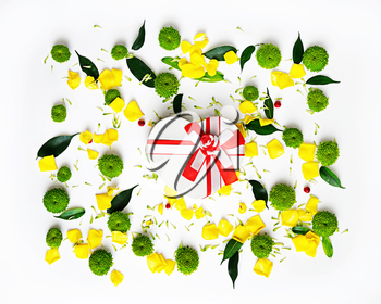 Gift in shape of heart with pattern from petals of rose and chrysanthemum flowers, ficus leaves and ripe rowan on white background. Overhead view. Flat lay.