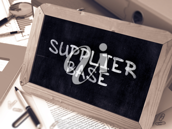 Supplier Base Handwritten on Chalkboard. Composition with Small Chalkboard on Background of Working Table with Ring Binders, Office Supplies, Reports. Blurred Background. Toned Image. 3D Render.