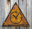 Royalty Free Photo of a Clock on a Rusty Sign Against a Wooden Wall