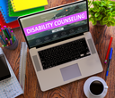 Disability Counseling Concept. Modern Laptop and Different Office Supply on Wooden Desktop background.