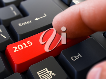 2015 Red Button - Finger Pushing Button of Black Computer Keyboard. Blurred Background. Closeup View.