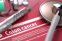 Colon cancer - Printed Diagnosis with Blurred Text on Red Background and Medical Composition - Stethoscope, Pills and Syringe. Medical Concept.