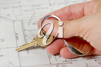 Hand holding a key over house blueprints