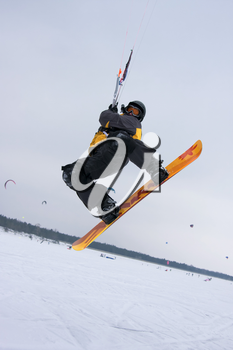 The snowkiter on the orange snowboard is jumping over the camera.