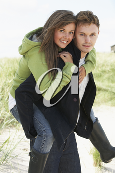 Young Man Giving Woman Piggyback In Dunes With Beach Hut In Distance