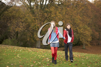 Romantic Teenage Couple Walking Through Autumn Landscape