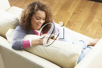 Woman Looking At Pictures On Digital Camera Relaxing Sitting On Sofa At Home