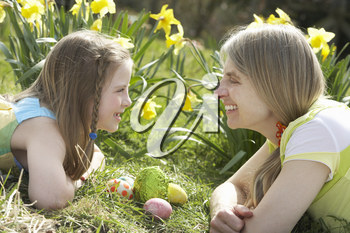 Mother And Daughter On Easter Egg Hunt In Daffodil Field