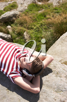 Young Man Listening To Music In Countryside On Headphones