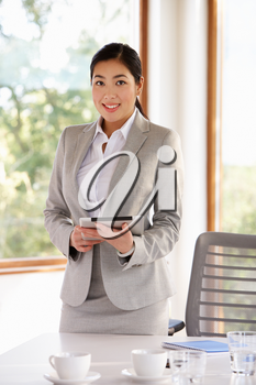 Businesswoman Standing In Boardroom With Digital Tablet