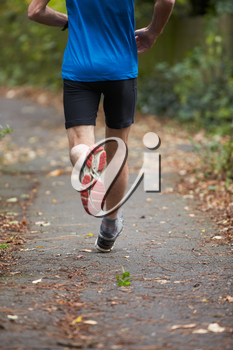 Close Up Of Jogger's Feet Running On Path