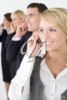 A businesswoman and a team of 2 women and a man out of focus behind her all talking on cell phones