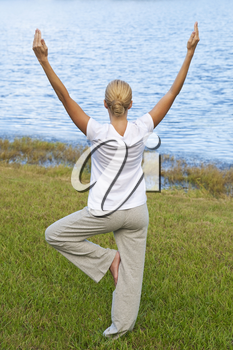 Rear view of a beautiful young blond woman practicing a yoga position by a tranquil blue lake