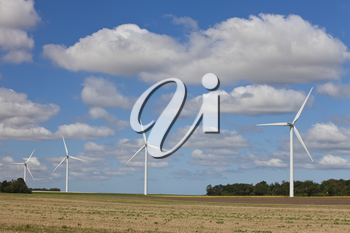 A farm of four wind turbines or windmills providing alternative sustainable green energy.