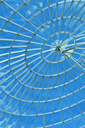 Bright blue sky seen through a modern architecture round or spiral window.