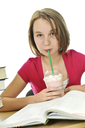 Teenage school girl studying with a milkshake