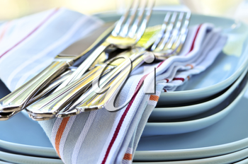 Table setting with stack of plates and cutlery