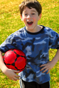 Portrait of a young cute happy boy holding a red soccer ball outside
