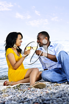 Young romantic couple celebrating with wine at the beach looking at each other