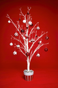 White modern Christmas tree decorated with various red and white themed christmas baubles (balls) on a red background.