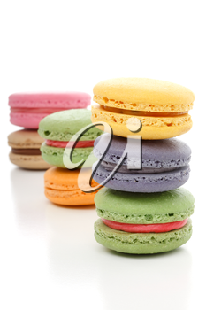 The delightful light fluffy texture melt in the mouth with a little bit of crunch and with a smooth buttercream filling - Mmmm macaroons.  Stacked on a white background. Various colours.