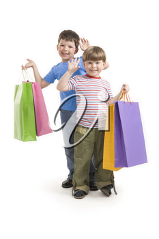Portrait of two happy boys holding colorful bags over white background