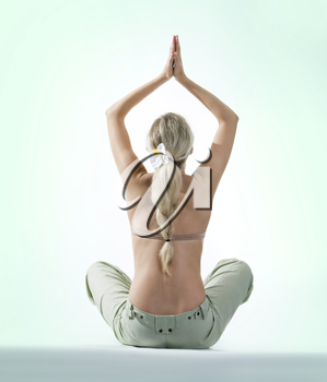 Back of beautiful woman sitting and keeping her hands raised with palms touching each other