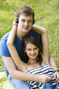 Portrait of happy guy holding his girlfriend on knees while both wearing headphones and enjoying music