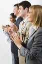Portrait of business team smiling and applauding on a white background