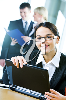 Young attractive office worker is looking at camera touching the laptop  on the background of her colleagues