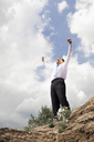 Photo of relaxed businessman standing and raising his arms outdoors in summer